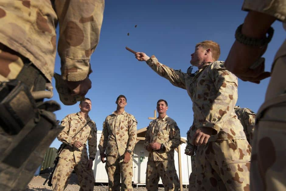 Australians soldiers playing two-up in Afghanistan, 2011 (ABC Licensed: CPL Ricky Fuller, Department of Defence)
