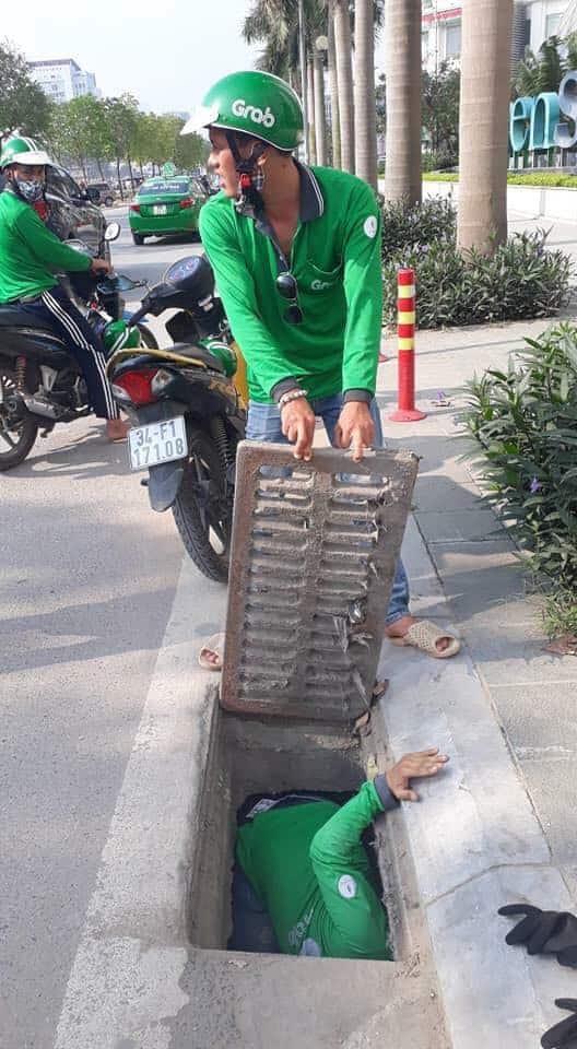 Tài xế GrabBike chui cống tìm thẻ ngân hàng giúp cô gái Anh - Ảnh 1.