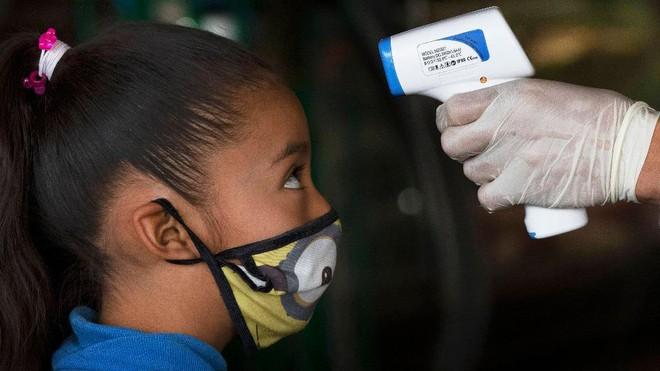 Học sinh được kiểm tra thân nhiệt trước khi vào trường /// AFP/Getty